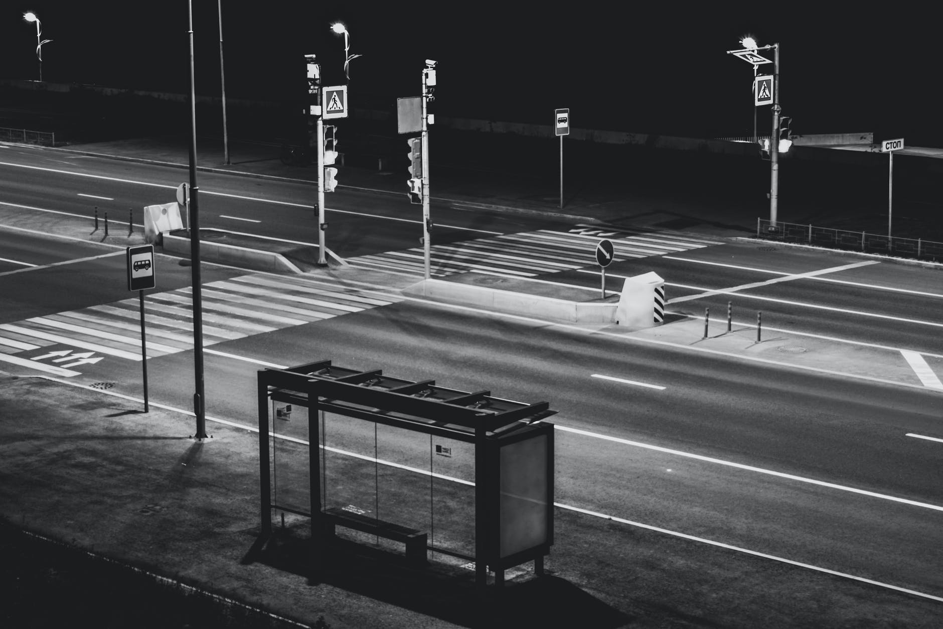 grayscale photography of waiting shed near open road at night