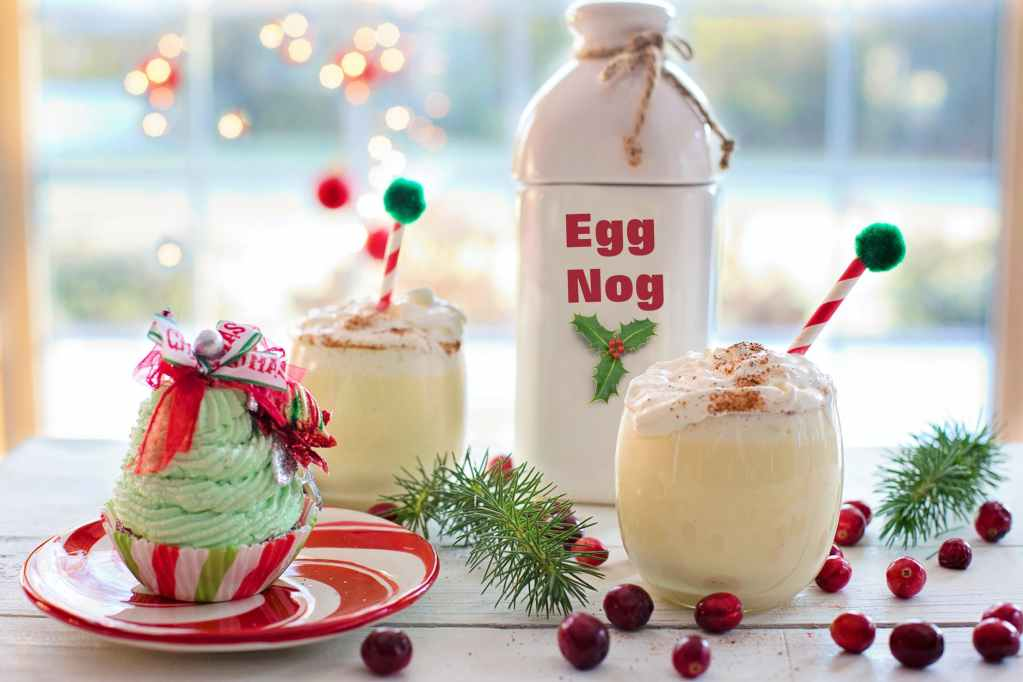 egg nog bottle near cupcake red berry fruits and ice cold drinks