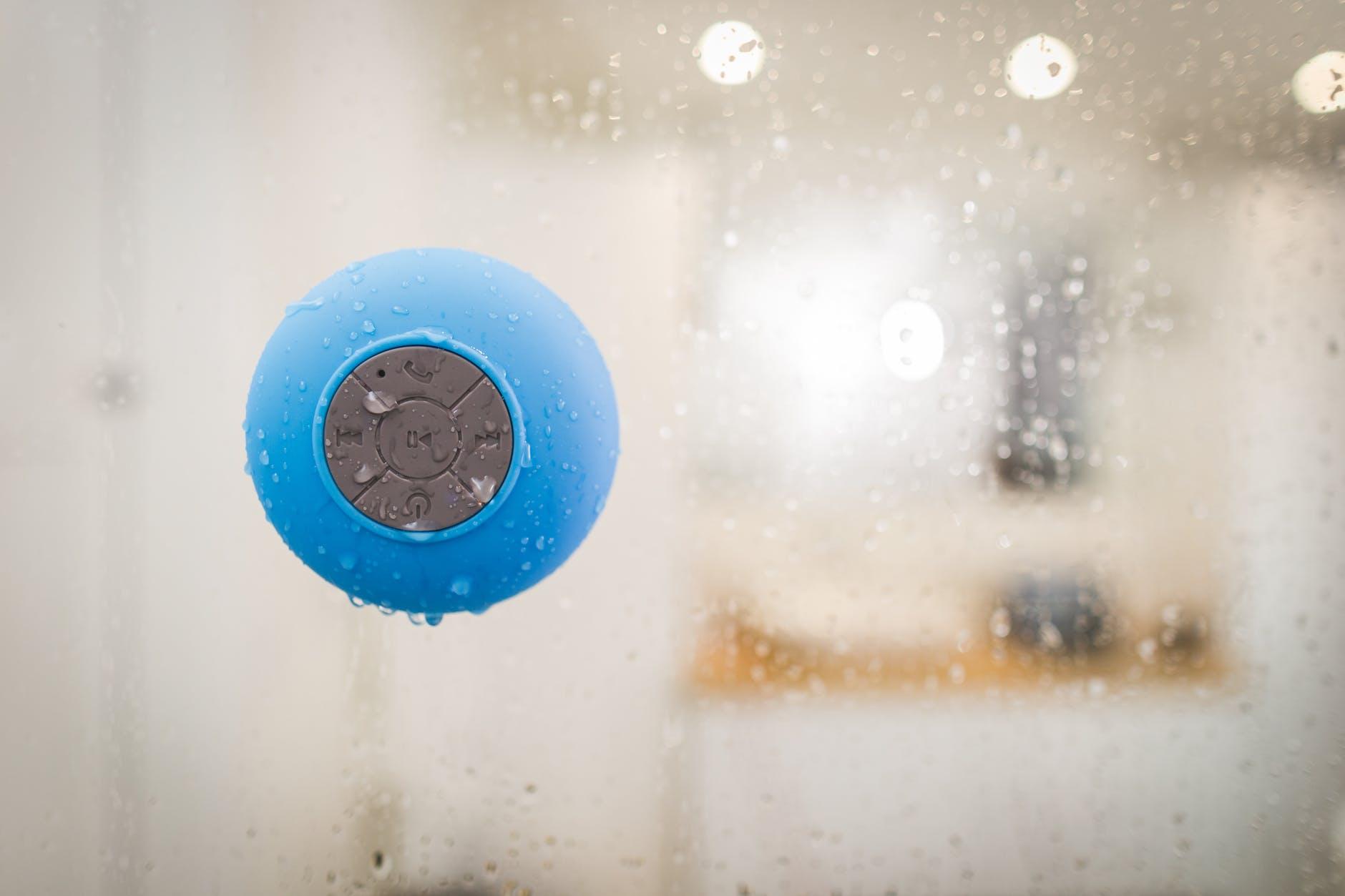 teal wireless speaker on clear glass