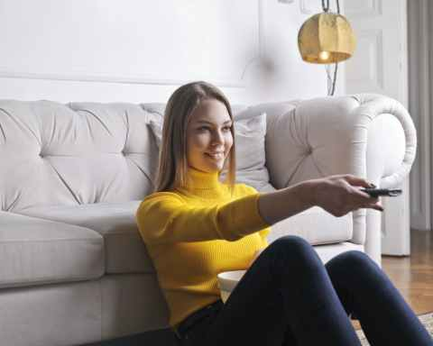 happy young relaxed woman watching tv at home