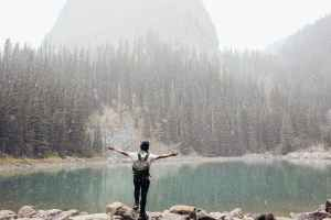man with backpack standing on stone near lake in highland