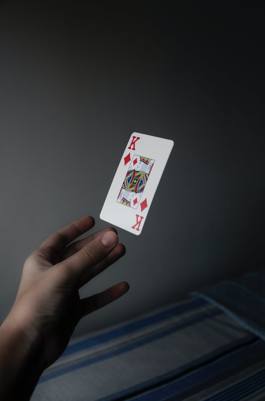person holding king of diamonds playing card