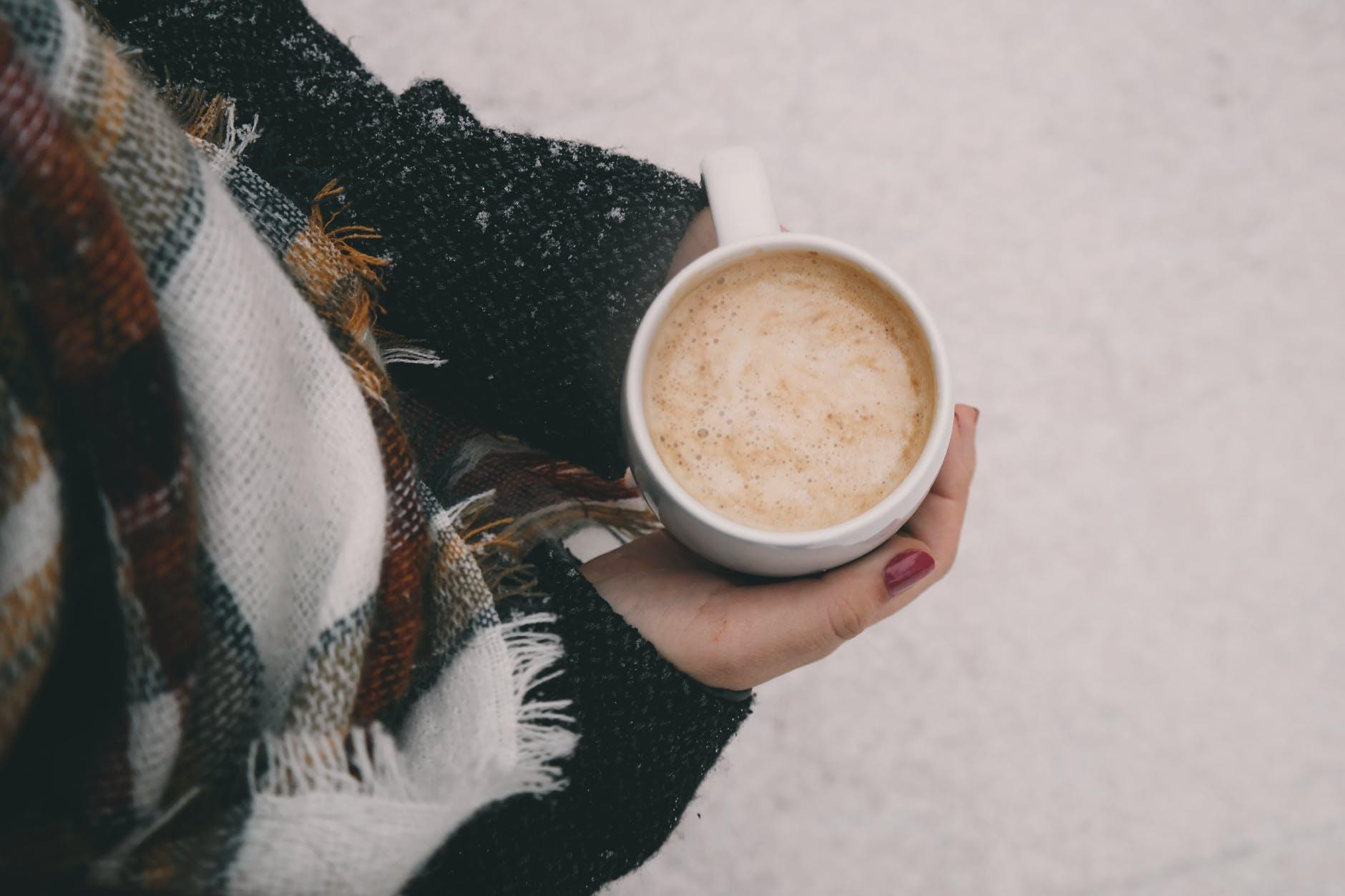 person holding mug of coffee