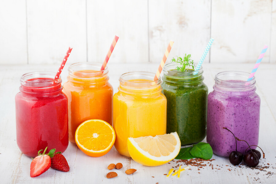 colourful fruit smoothies surrounded in fruit
