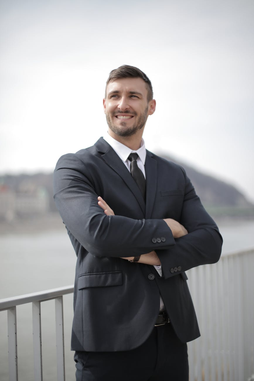 man in black suit jacket standing near railings